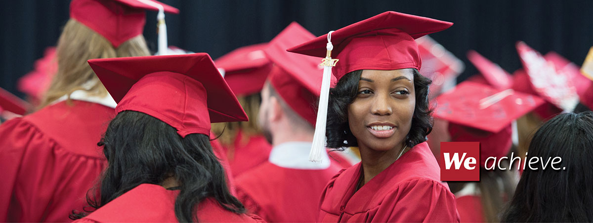 Student at December 2017 commencement ceremony in red regalia.