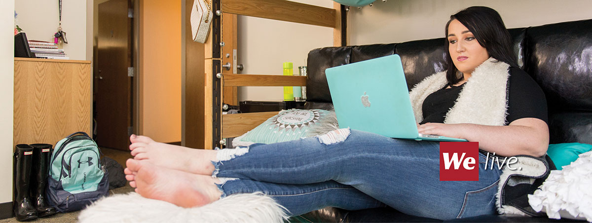 Student sitting on bed in SVSU residence hall interacting with laptop computer
