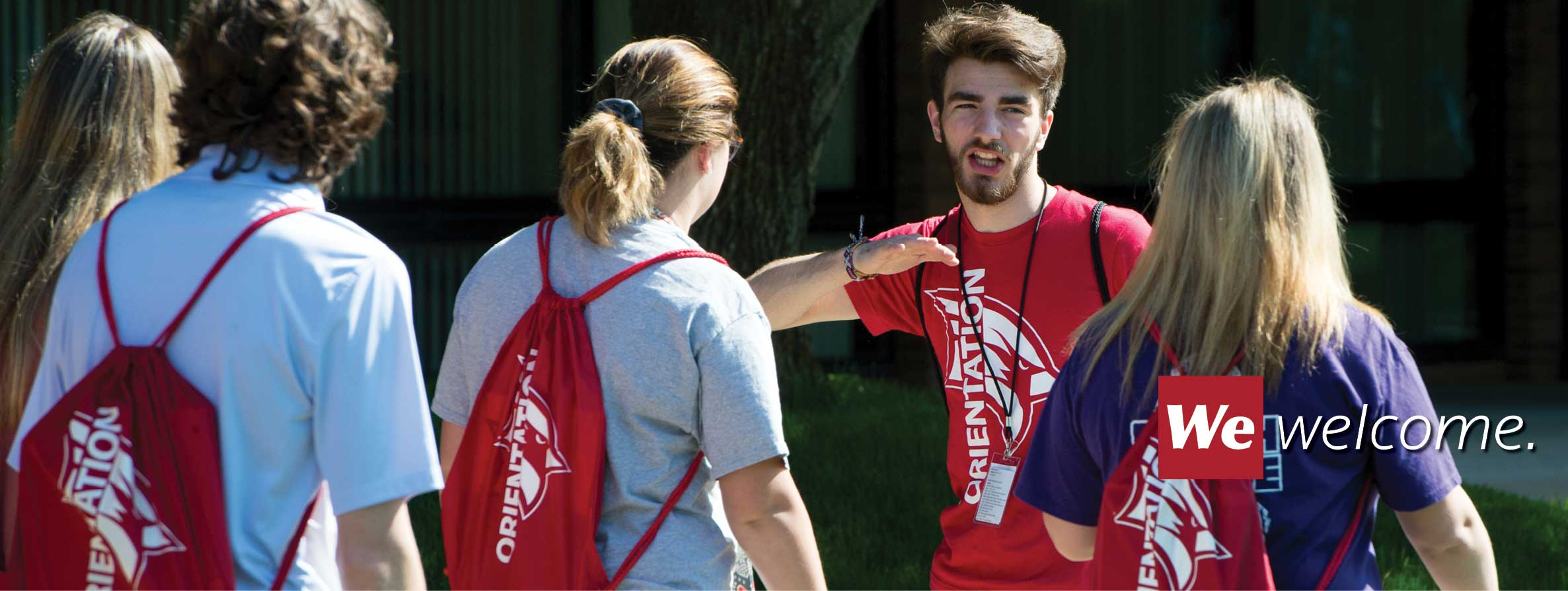 An orientation leader talks to students with orientation backpacks on their backs. We welcome.