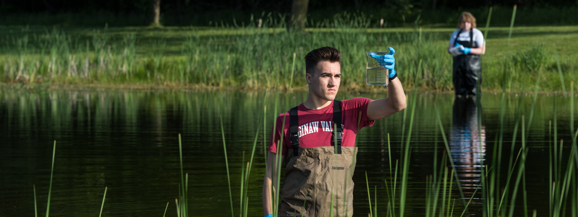 Image of student practicing techniques to capture water samples utilizing campus ponds.
