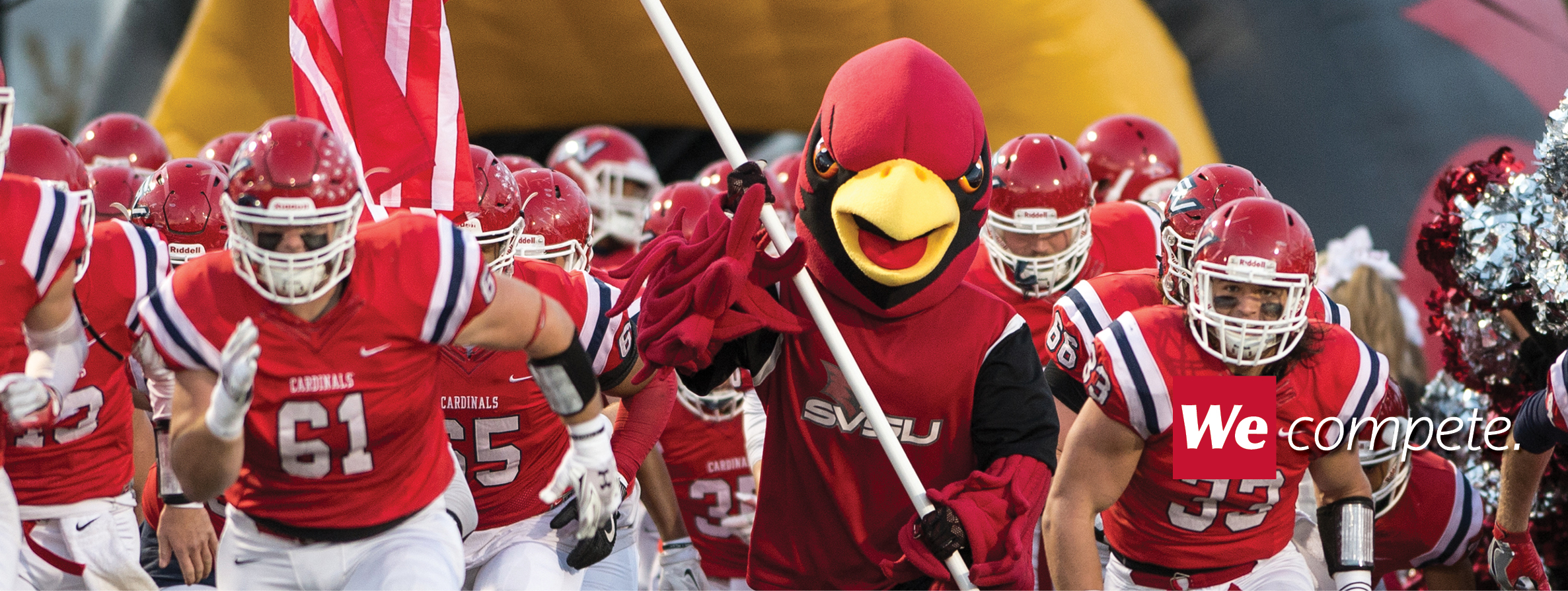 Football team running onto field holding SVSU flag with SVSU mascot Coop.