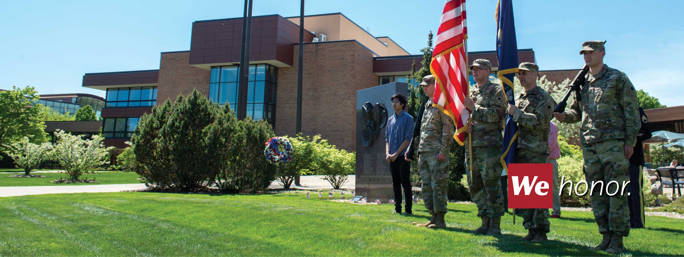 Four military color guard soldiers holding the US and Michigan flags at the Eaton Memorial outside of the Marshall M Fredericks Musuem and Wickes Hall.