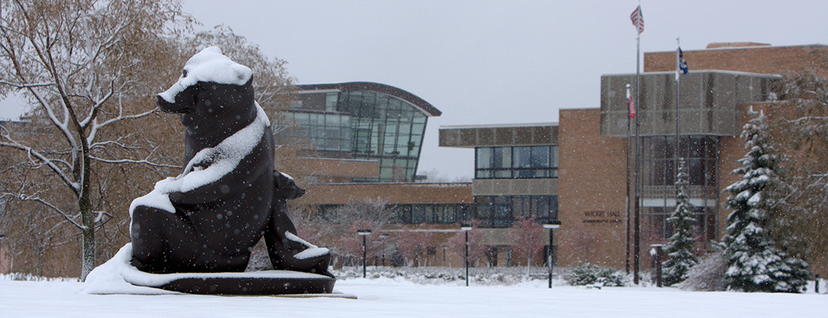 Image of Marshall M. Fredricks' two bears sculpture, covered in snow with SVSU's campus in the background