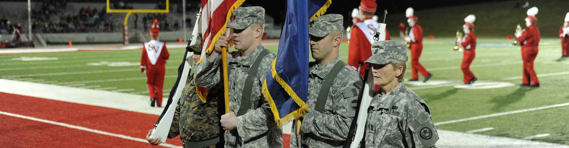 Military members carry flags before a SVSU football game