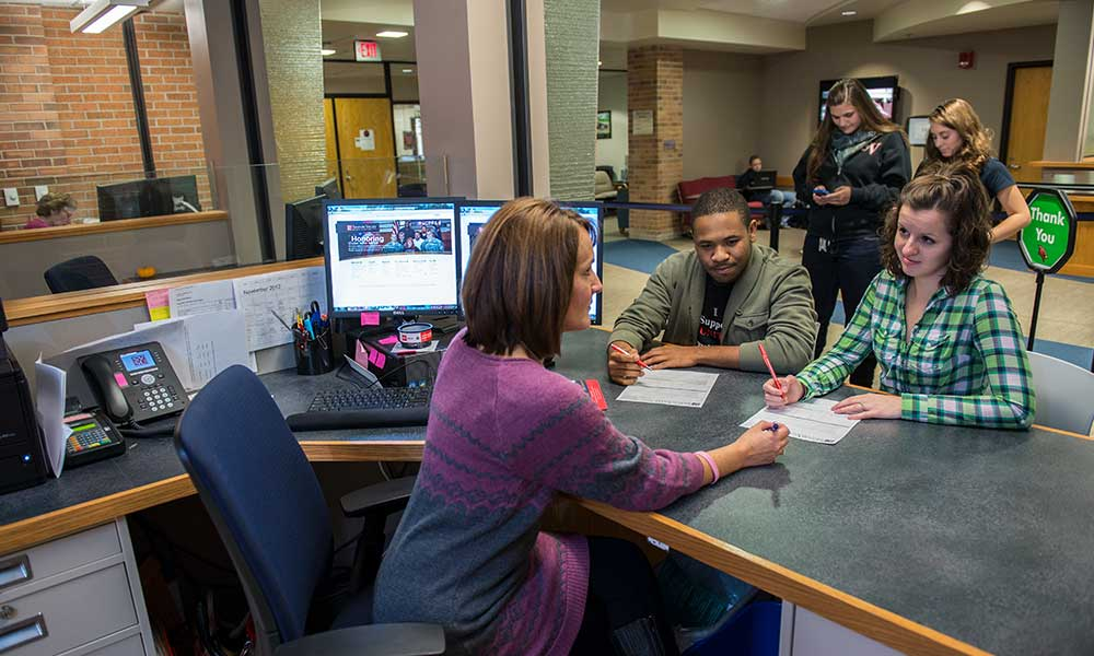 students getting assistance at registrar and financial aid office
