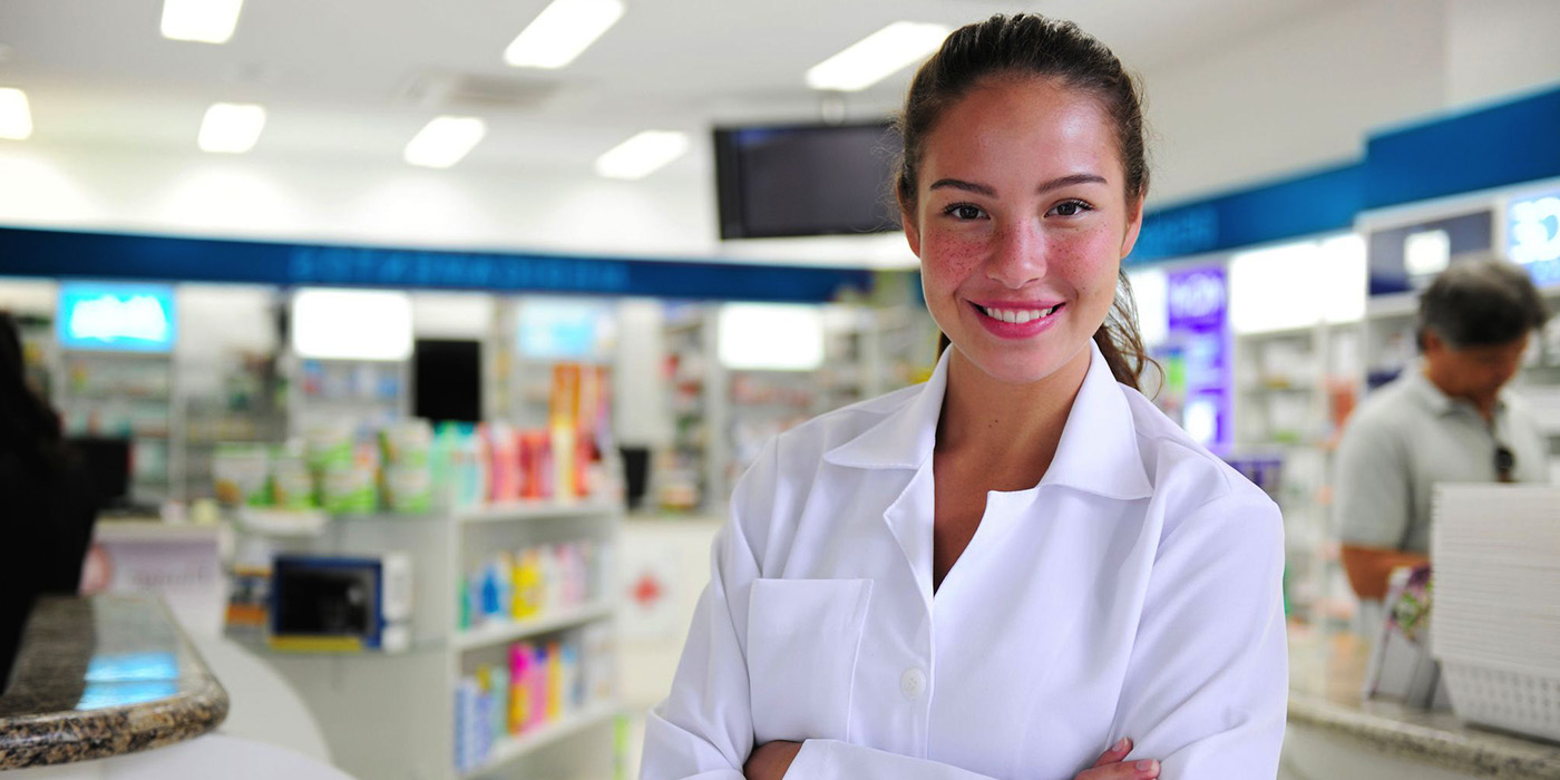 A pharmacist standing at the desk of a pharmacy smiling at the camera