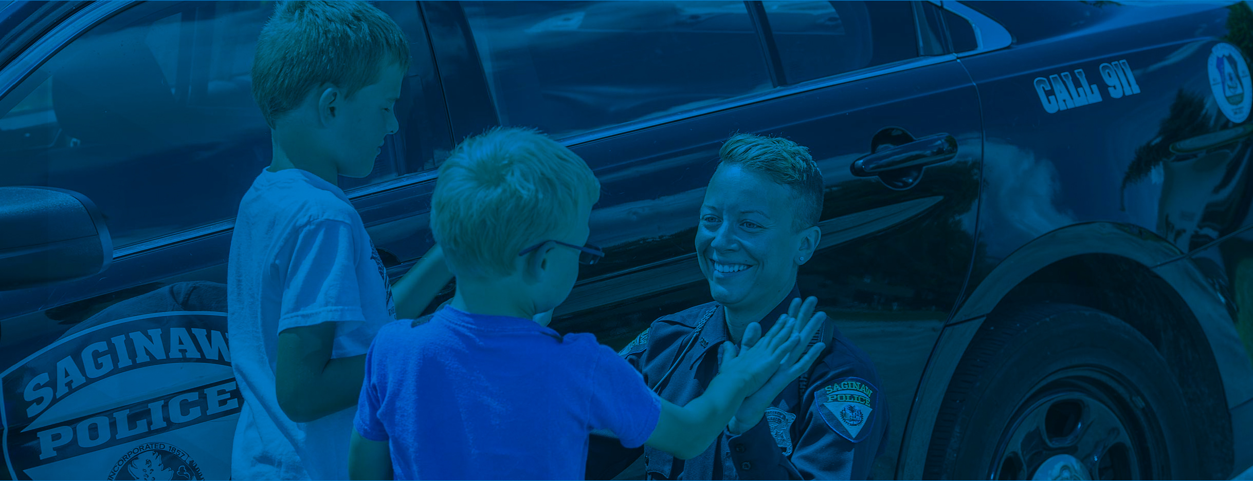 Officer Samm Buth with two children by her police vehicle.