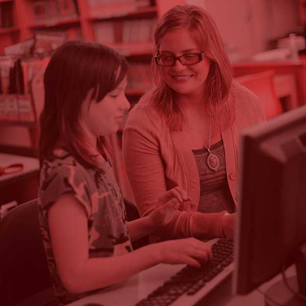 Student teacher mentoring a student on a computer