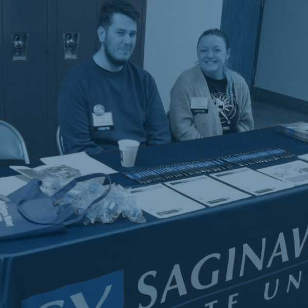 Students set up at table in a school to promote svsu history programs