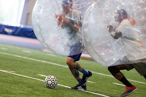 students playing blow up soccer in the field house