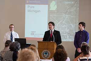 Andrew Miller, SVSU associate professor of geography, presents research showing blight removal in Saginaw has contributed a drop in crime in the city and its neighbors. Miller spoke at the Reinventing Saginaw symposium at the Bancroft building in downtown Saginaw May 26, 2015.