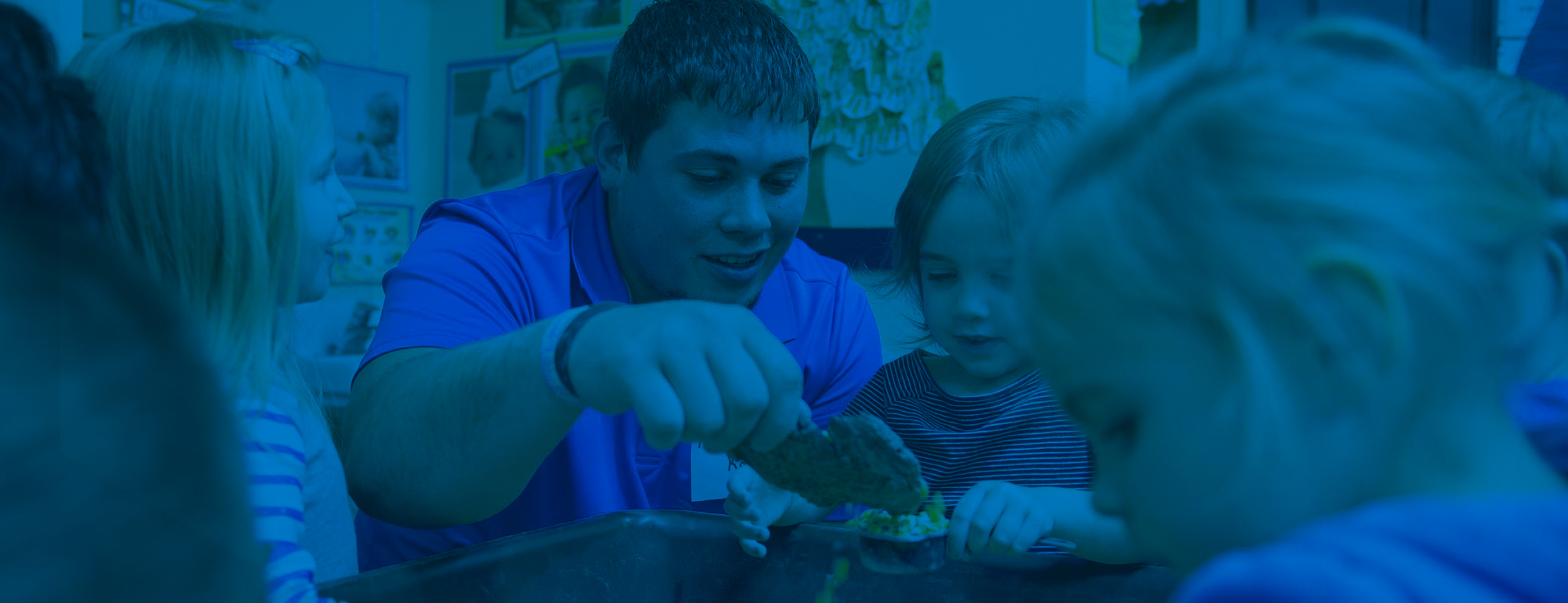 A male SVSU early childhood student works with young children at Growing Years Daycare.