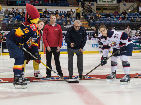 "President Bachand drops the ceremonial ""first puck"" at the Saginaw Spirit Hockey game. Beside him are Student Association president Cody McCay and Coop."