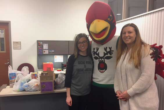 Sara Schuster and Amanda Haas (pictured with Coop), deliver several bags of non-perishable food items to the pantry.