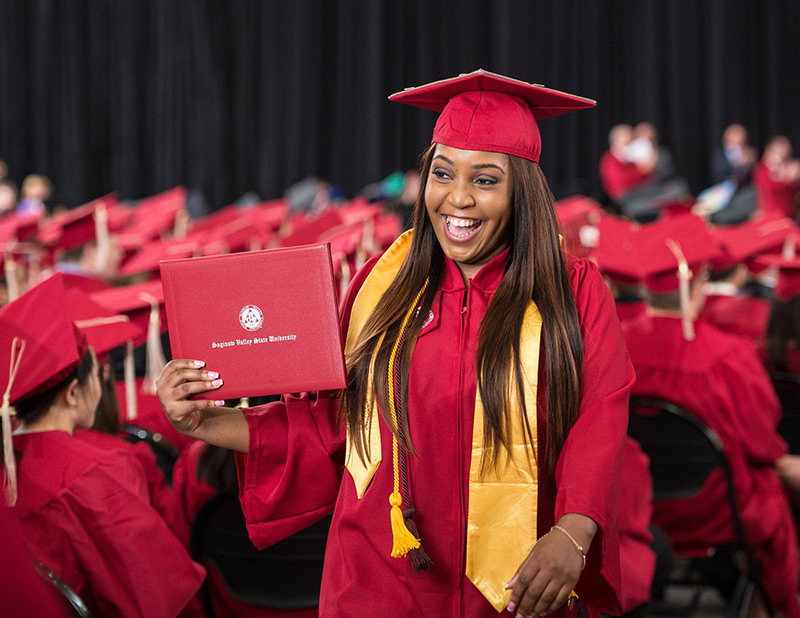 Undergraduate student wearing red commencement regalia with red motorboard and yellow cords celebrates at Commencement with diploma jacket in hand and a huge smile on her face.