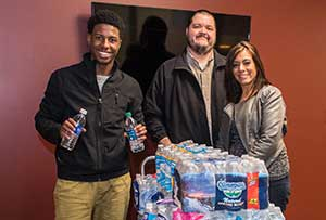 Team One Credit Union representatives Andrea Sanchez and Dante Green donate water for the Flint Water Crisis.