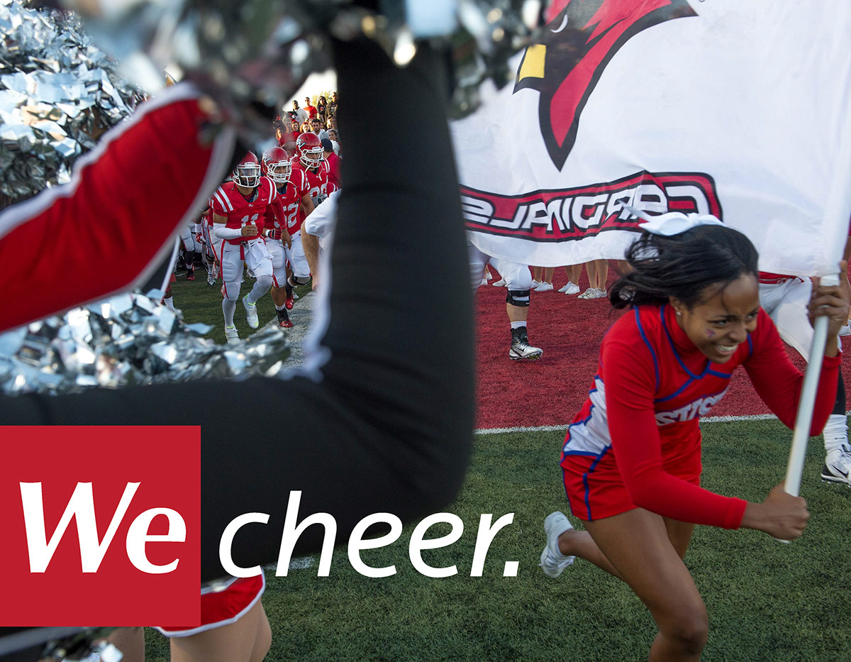 Photo of SVSU cheerleader holding SVSU flag running through tunnel of people with the words We Cheer in the lower left corner.