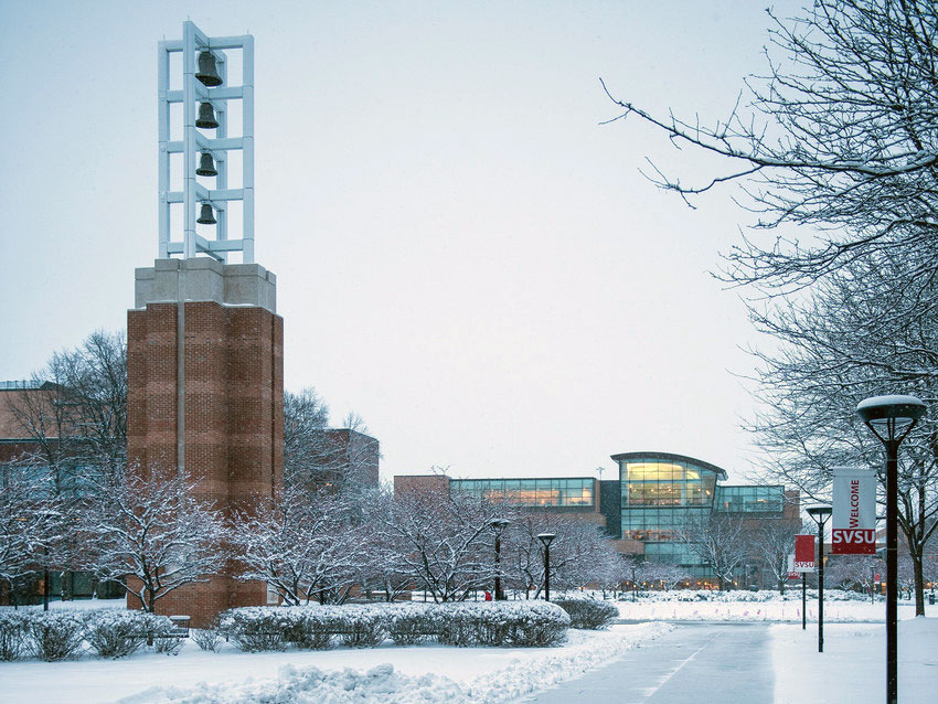Snow covered interior of campus looking over bell tower and side walk lined with signs that say welcome to SVSU.