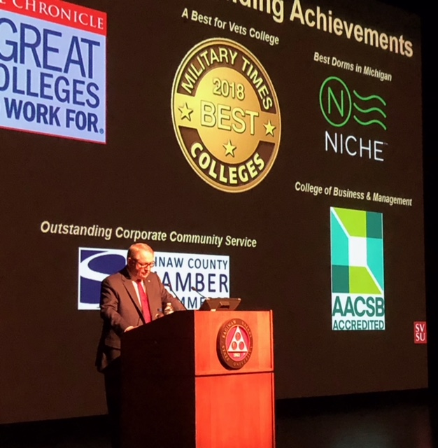 President Bachand at podium with Outstanding Achievement logos behind him: The Chronicle Great Colleges to Work For, Military Times 2018 Best Colleges, Best Dorms in Michigan for Niche, AACSB Accreditation for College of Business, and Outstanding Corporate Community Service and Saginaw County Chamber of Commerce.
