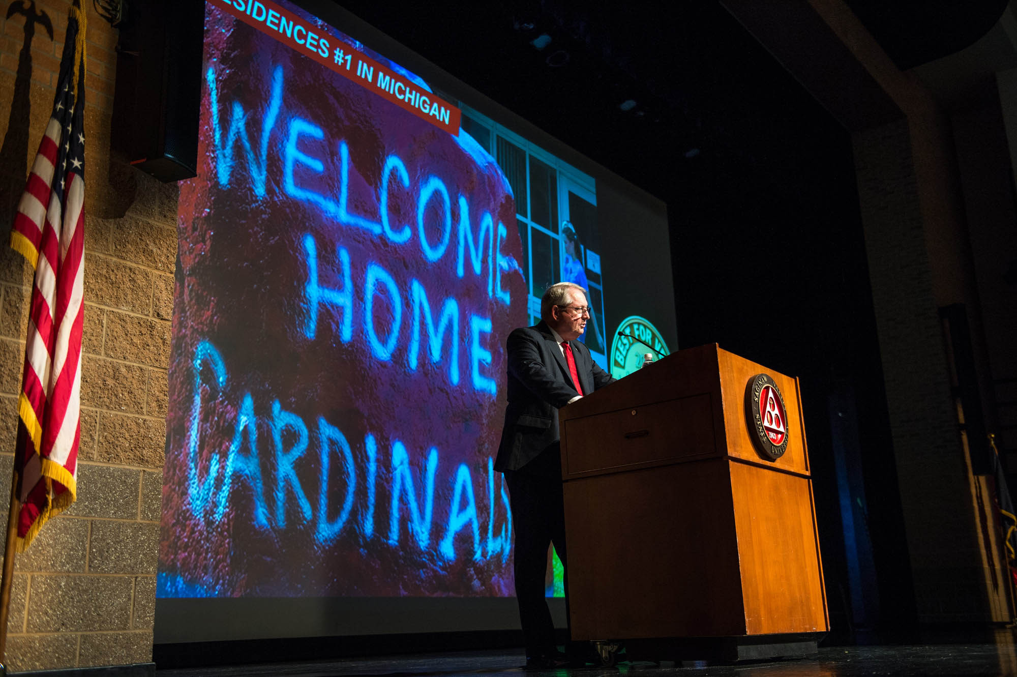 President Bachand at podium with Welcome Home Cardinals message in back
