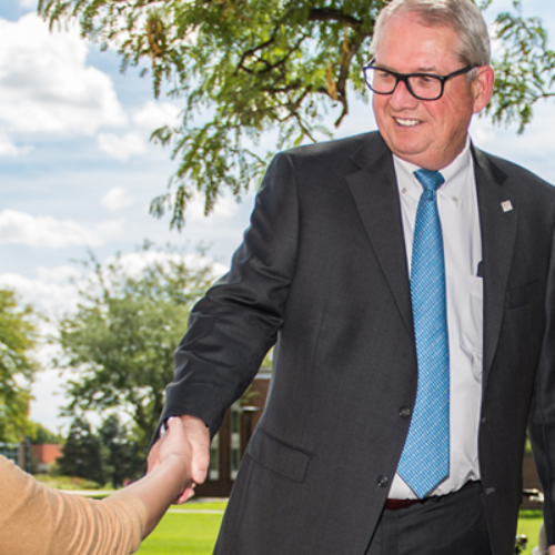 President Bachand shakes hands with students