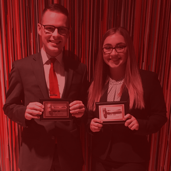 A pair of Moot Court students holding awards from competition
