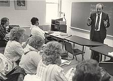 A man in a classroom lecturing in front of a blackboard